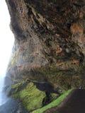 Klippagrotta under en vattenfall, Island Royaltyfri Foto