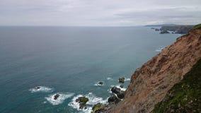 Klippan glider in i havet Arkivfoto