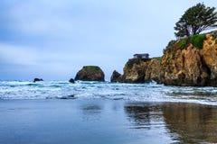 Klippan på slutet av stranden har det enkla hus- och singelträdet överst Arkivfoton