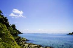 Klippan som täckas med tjock lövverk, och turkos färgar havsvatten som omger ön royaltyfria foton