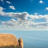 Klippbrants- over hav och blå himmel Fotografering för Bildbyråer