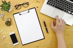 Klippbrettmodell mit der Mannhand und Notizbuch, Smartphone, Bürozubehör auf hölzernem Schreibtischhintergrund Finger auf Stockfoto