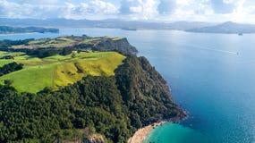 Klippe auf einem sonnigen Strand mit Ackerland auf dem Hintergrund Coromandel, Neuseeland Lizenzfreie Stockfotografie