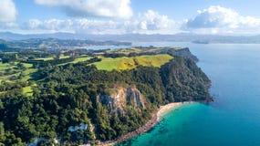 Klippe auf einem sonnigen Strand mit Ackerland auf dem Hintergrund Coromandel, Neuseeland Stockfotografie