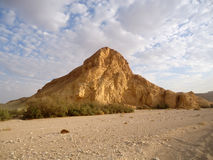 Klippe in der Wüste gegen einen blauen Himmel mit Wolken Lizenzfreies Stockbild