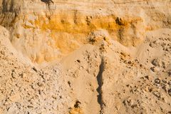 Klippe des gelb-orangeen braunen Sandbodenlehms unter dem hellen sonnigen Tag Alte Backsteinmauer Lizenzfreies Stockbild
