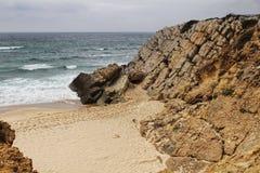 Klippen bij Guincho-strand onder bewolkte hemel in Portugal royalty-vrije stock afbeelding