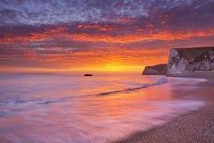 Klippen an Durdle-Tür setzen in Süd-England bei Sonnenuntergang auf den Strand Lizenzfreies Stockfoto