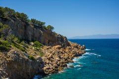 Klippen en bomen tegen de Middellandse Zee op een zonnige dag Royalty-vrije Stock Afbeelding