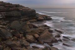 Klippen und Flusssteine treffen das Meer Stockfoto