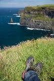 Klippen van Moher, Ierland, rotsachtige overzeese kust, benen in wandelingsschoenen Stock Foto