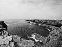 Klippen van stenen die zich met de oceaan en de hemel met sommige wolken vormen die de macht van god met aard tonen royalty-vrije stock foto