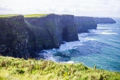 Klippen von Moher in Alantic-Ozean in West-Irland mit den Wellen, die gegen die Felsen zerschlagen lizenzfreies stockbild