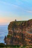 Klippen von Moher mit Kontrollturm am Sonnenuntergang in Irland. Stockfotografie