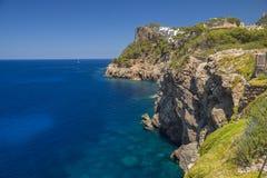 Klippenküstenlinie mit ruhigem tiefem blauem Meer Lizenzfreies Stockfoto