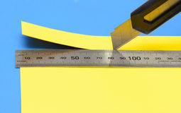 Klipper av ett stycke av gulingpapper med en kniv och en rostfritt stållinjal Royaltyfri Foto