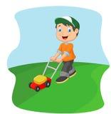 Klippgräs för ung man med en pushgräsklippare Royaltyfri Fotografi
