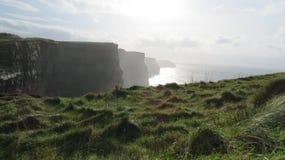 Klippor av Moher bredvid rullningsgräsplan Arkivbilder