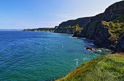 Klippor längs irländsk kust bredvid den mycket lilla Carrick-a-rede ön Arkivbilder