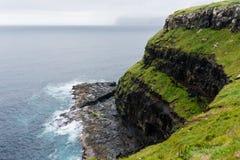 Klippor nära den Gasadalur vattenfallet i den Vagar ön på faroen royaltyfri bild