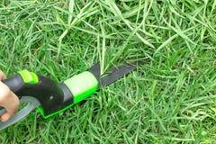 Klippt gräs med grässax Arbeta i trädgården arkivfoton