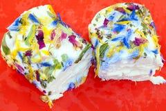 Klippt mjuk vit ost som t?ckas i ?tliga blommor royaltyfri fotografi