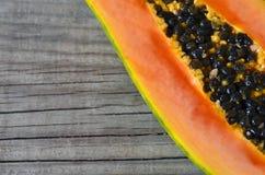 Klippte tropisk frukt för den nya mogna organiska papayaen i halva på gammal träbakgrund Sunt äta, bantar eller strikt vegetarian Royaltyfria Bilder