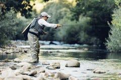 Klipsk fiskare som använder den flyfishing stången Fotografering för Bildbyråer
