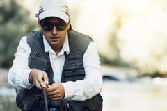 Klipsk fiskare som använder den flyfishing stången Royaltyfria Bilder