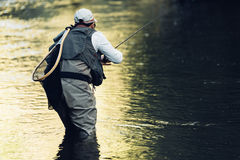Klipsk fiskare som använder den flyfishing stången Royaltyfri Foto