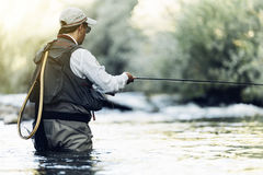Klipsk fiskare som använder den flyfishing stången Arkivfoto
