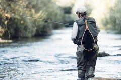 Klipsk fiskare som använder den flyfishing stången Royaltyfria Foton