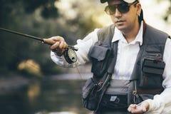 Klipsk fiskare som använder den flyfishing stången Royaltyfri Bild