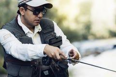 Klipsk fiskare som använder den flyfishing stången Arkivbild