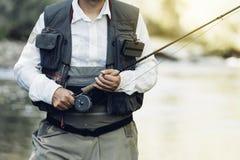 Klipsk fiskare som använder den flyfishing stången Arkivfoton