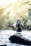 Klipsk fiskare som använder den flyfishing stången Arkivbilder