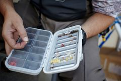 Klipsk fiskare som väljer en liten fluga från en ask Royaltyfri Bild