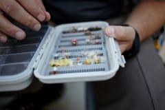Klipsk fiskare som väljer en specifik fluga från en ask Arkivbild