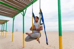 Klipsk yoga, mannen som gör yoga, övar på havsbakgrunden Sport och sunt begrepp arkivfoto
