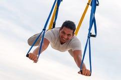 Klipsk yoga, mannen som gör yoga, övar på himmelbakgrunden Sport och sunt begrepp arkivfoton