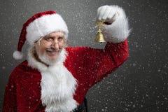 Klirr sätta en klocka på Klocka för Santa Claus innehavmetall i hans hand royaltyfria foton