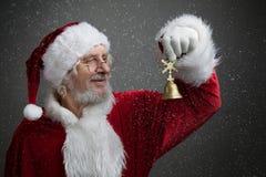 Klirr sätta en klocka på Klocka för Santa Claus innehavmetall i hans hand arkivfoton