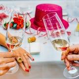 Klirra exponeringsglas av champagne i händer på partiet royaltyfri fotografi