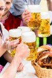 Klirra exponeringsglas med öl i bayersk bar royaltyfri foto