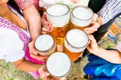 Klirra exponeringsglas med öl i bayerskt öl arbeta i trädgården arkivfoto