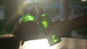 Klirrende Flaschen des glücklichen Paars durch die Sonne mit Blendenfleckeffekten im Café, während Sonne untergeht Langsame Beweg stock video footage