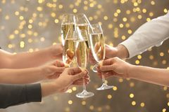 Klirrende Gläser der Leute mit Champagner gegen unscharfe Lichter Bokeh Effekt stockfotos