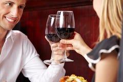 Klirrende Gläser der Paare Rotwein Stockfoto