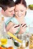 Klirrende Gläser der reizenden Paare beim Kochen von Teigwaren Stockfotografie