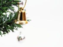 Klirrklockan som hängs på grön jul, sörjer trädfilialen på vit bakgrund Royaltyfri Bild